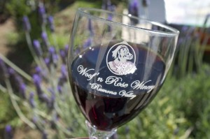 Woof'n Rose logo glass with dark red wine against a backdrop of lavender flowers.